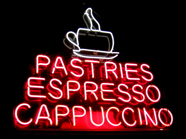 Neon words above downtown San Diego cafe door read Pastries Espresso Cappuccino.