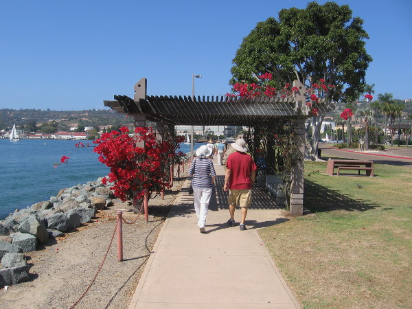 People walk along the pathway which stretches down narrow Shoreline Park. Grass, benches and picnic tables invite both locals and tourists.