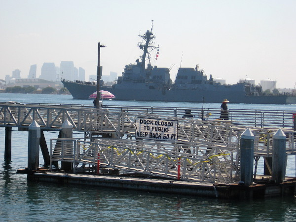 A large Navy warship entering San Diego harbor is seen beyond the Shelter Island pier. Downtown skyscrapers appear misty in the background.