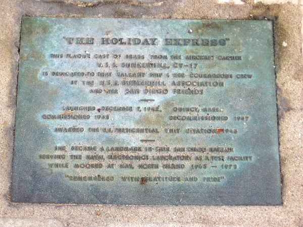 At the base of the flagpole: The Holiday Express. This plaque cast of brass from the aircraft carrier USS Bunkerhill CV-17 is dedicated to that gallant ship and her courageous crew.