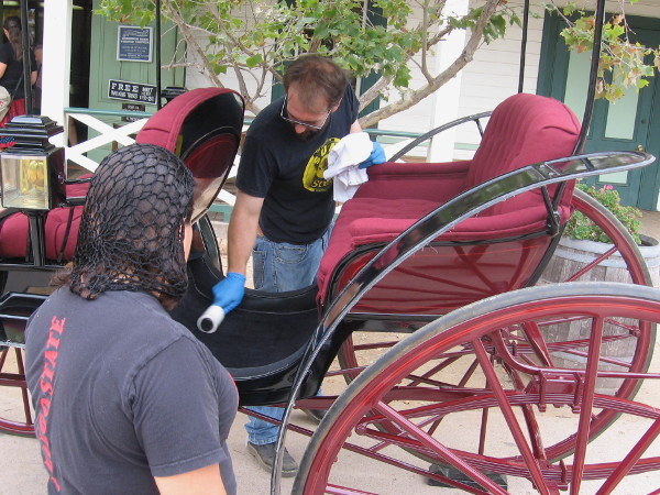 Preparing an old Stanhope Park Phaeton, parked with other buggies and carriages in front of the Robinson-Rose House Visitor Information Center.
