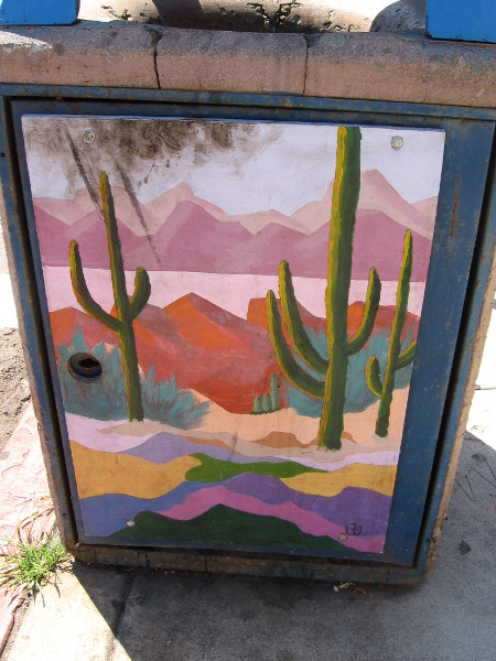 Urban art on a La Jolla trashcan shows a boldly colorful Southwestern scene, with mountains and cacti.