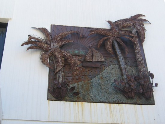 Some interesting metal artwork above a store entrance depicts a sailboat and palm trees.