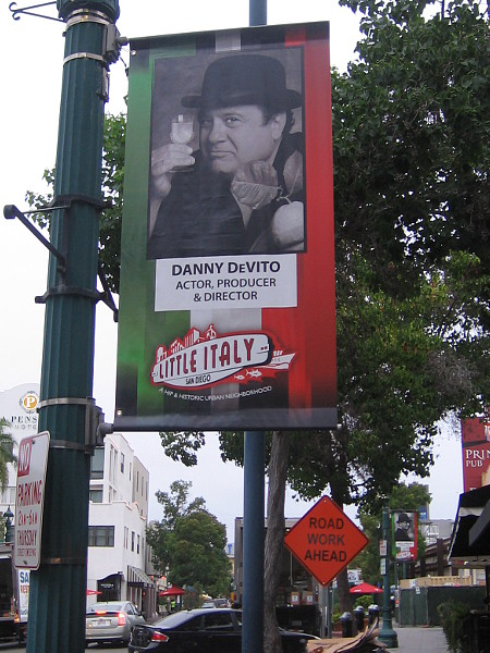 Little Italy street banner shows actor Danny DeVito enjoying a drink.
