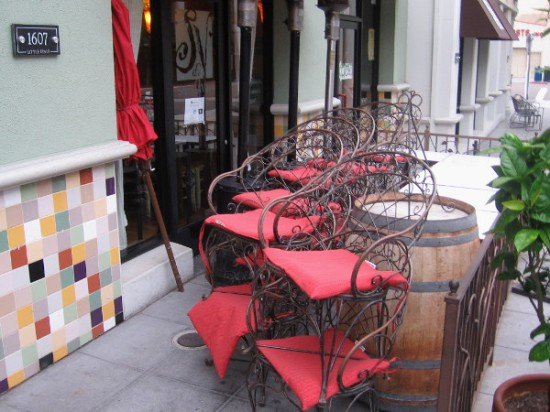 An umbrella and chairs that will soon be arranged for casual alfresco dining.
