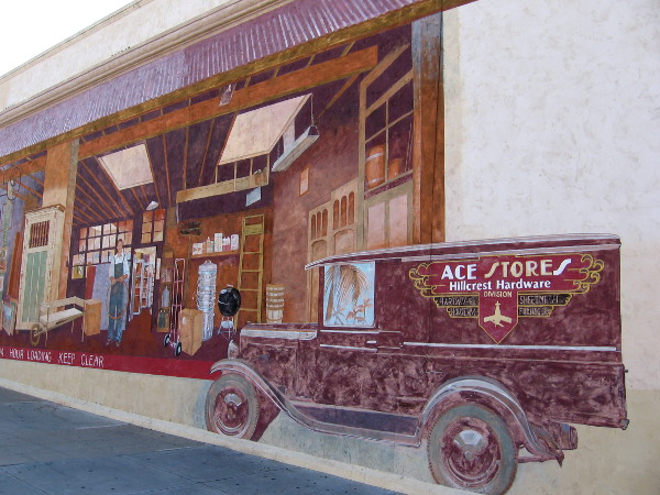 The cool, nostalgic trompe l'oeil painting depicts an old-fashioned hardware store loading dock, complete with realistic Ace Stores delivery truck.