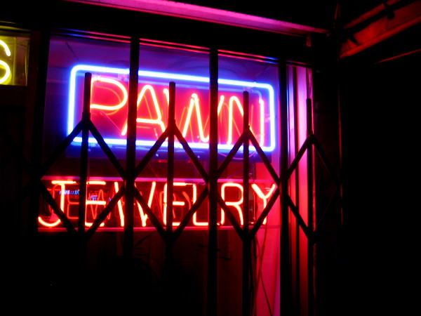 Classic neon signage is often seen in pawn shop windows.