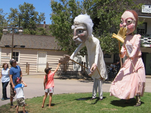 Girl greets large puppet Mark Twain and Emily Dickinson at 2015 TwainFest in Old Town San Diego State Historic Park!