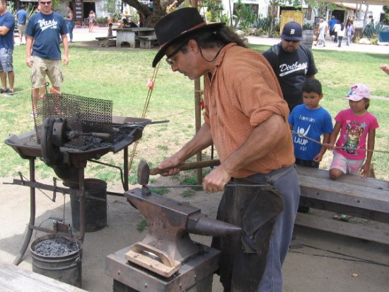 A patient blacksmith bangs away on some hot metal as he fashions a thin, pointed nail.