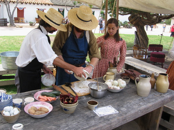 These folks in historical costume are busily preparing some biscuits, a common food in the early days of San Diego.