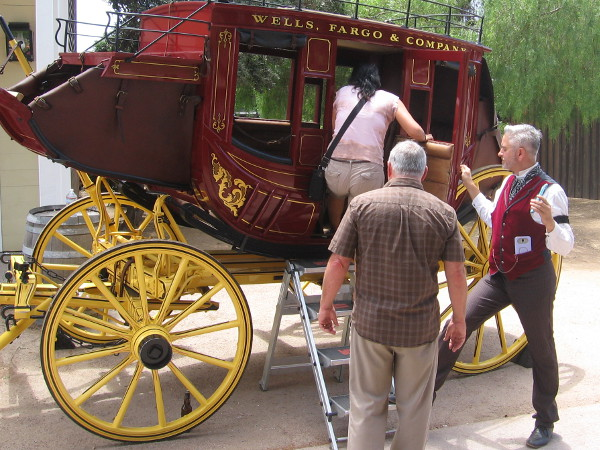 Wells Fargo employee, from the agent's office museum in the Colorado House, helps Old Town visitors into a stagecoach for a photograph.