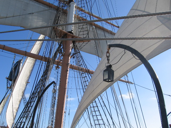White sails, yards, shrouds, ropes and blue sky.