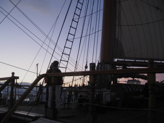 The sky through ship's rigging is tinged orange, red, purple and gold.