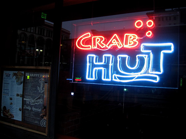 Crab Hut invites hungry passersby with its neon logo.