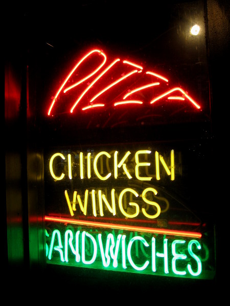 Eye-catching neon sign informs all who pass by that pizza, chicken wings and sandwiches are on the menu.