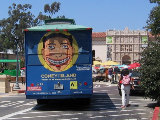 Grinning face of Tillie, symbol of Coney Island, on the back of a tour bus heading toward the San Diego Museum of Art in Balboa Park.