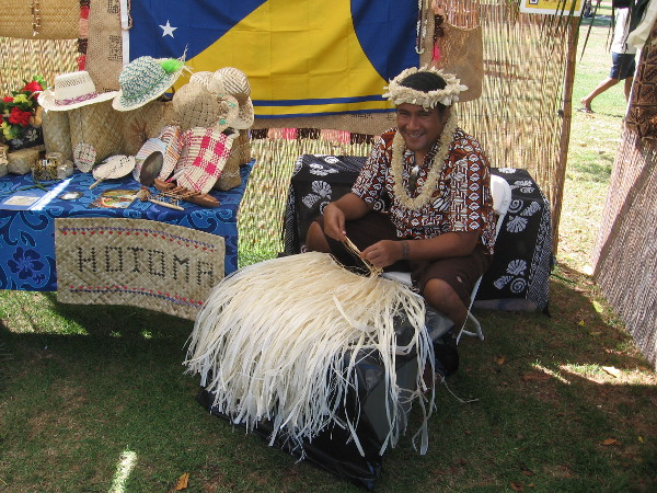 Friendly guy at Pacific Islander Festival representing Tokelau shows how skirts are fashioned using natural fibers.
