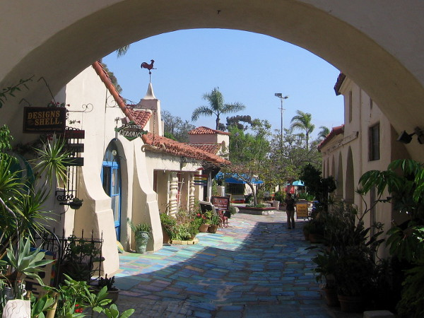 A peek through an arch into Spanish Village from the small north parking lot.