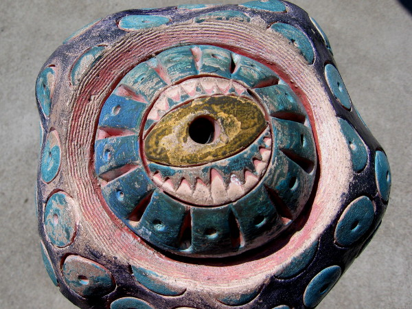 A single artistic eyeball painted pink, yellow, purple and blue. The ceramic post-toppers have forms that are very organic.