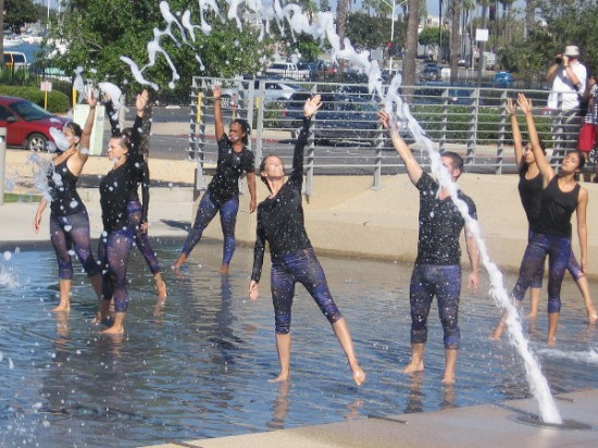 Dancers in the fountain at San Diego's Waterfront Park reach skyward during the Trolley Dances.