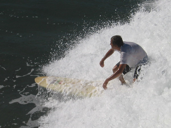 Photo of guy surfing near the pilings of the awesome Ocean Beach Municipal Pier.