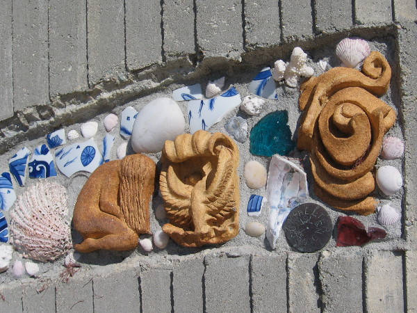 Bits of sea shells, broken pottery and cultural motifs in a curving concrete wall.