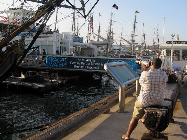 Photographer near the HMS Surprise takes photos of many masts along the waterfront beyond the Maritime Museum of San Diego.