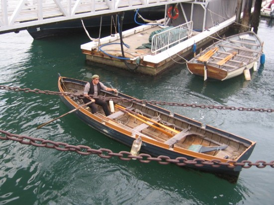 Gentleman from the Maritime Museum rows a longboat under ramp which leads to the HMS Surprise and other historic ships on San Diego Bay.