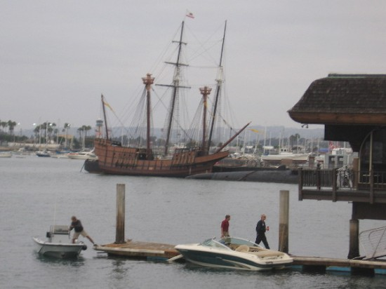 Full size replica of historic Spanish galleon San Salvador seen beyond dock of Anthony's Fish Grotto on San Diego's Embarcadero.