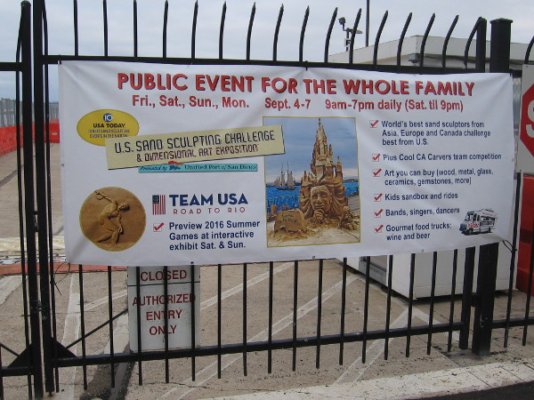 Banner on fence at B Street Pier near Cruise Ship Terminal promotes the 2015 U.S. Sand Sculpting Challenge and Dimensional Art Exposition in San Diego.