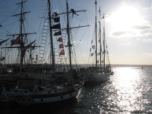 Falling sun behind evening clouds and picturesque dark masts on San Diego Bay at the Festival of Sail.