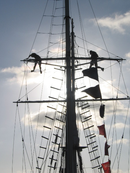 Two crewmembers work high in the rigging of the Amazing Grace tall ship.
