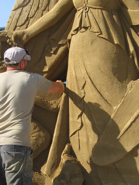 A masterpiece of sand is being created as the public watches and takes photographs.