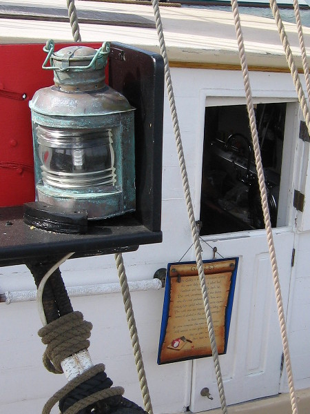 Ship's navigation light and galley. Signs on the Pilgrim describe life on the sea a couple centuries ago, when Two Years Before the Mast was written by Dana.