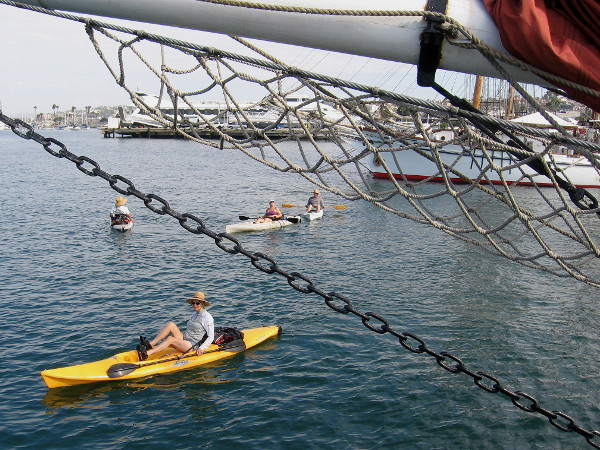 Kayaks on the smooth water cruise past a collection of very cool tall ships.