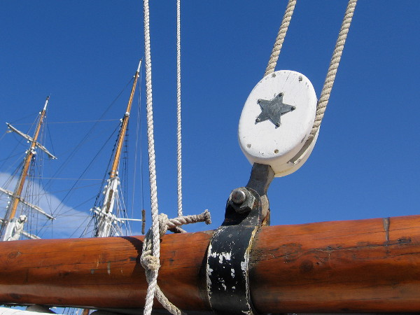 Star motif on a block used by a single rope in the complicated rigging. Masts of another nearby tall ship rise in the background.