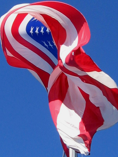 American flag in deep blue sky curls in the pleasant sea breeze.