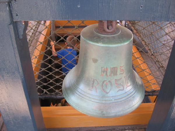 Written on the ship's bell is HMS Rose, the original name of the Surprise.