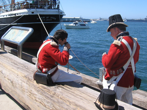 Two members of the Royal Guard enjoy a drink and snack on San Diego's Embarcadero during the Festival of Sail. They must be shore leave.