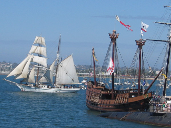 White sails, wooden ships, blue sky and living visions of maritime history.