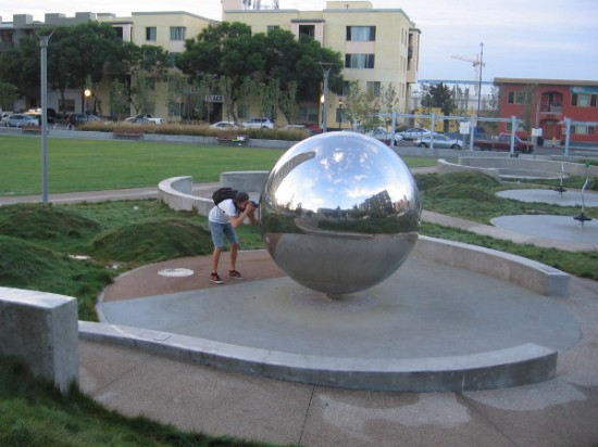 Photographer records cool reflections in one of the large stainless steel spheres in Fault Line Park.