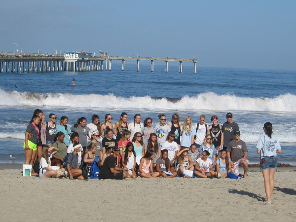 Many Coastal Cleanup Day volunteers assembled for a photograph, with the Pacific Ocean and long Ocean Beach Municipal Pier in the background.