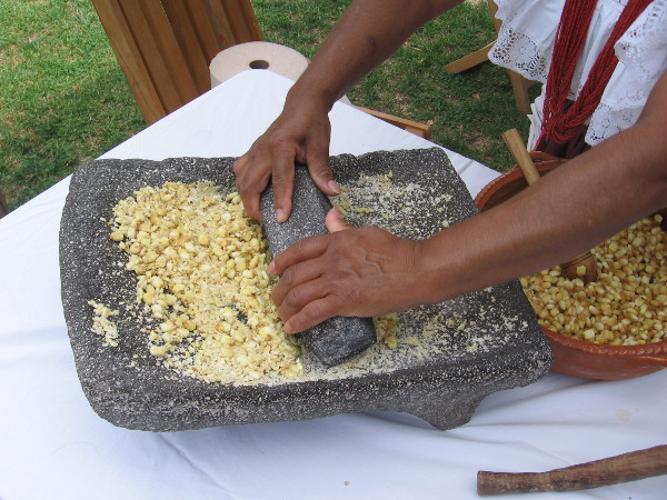 A super nice lady demonstrates grinding corn with a stone metate, a common practice long ago.