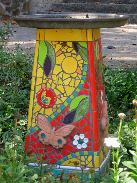 An artistic bird bath in the garden depicts leaves, flowers and butterflies, naturally!