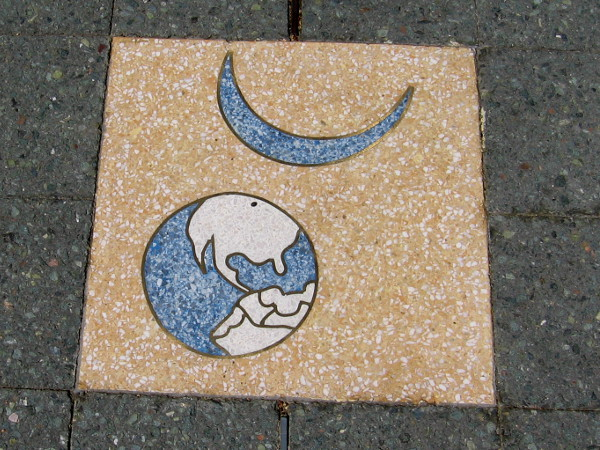 The Earth and a crescent moon. One of 26 terrazzo inserts arranged in a circle in the entrance plaza of the Balboa Park Activity Center. Created in 1999 by artist Joyce Cutler-Shaw.