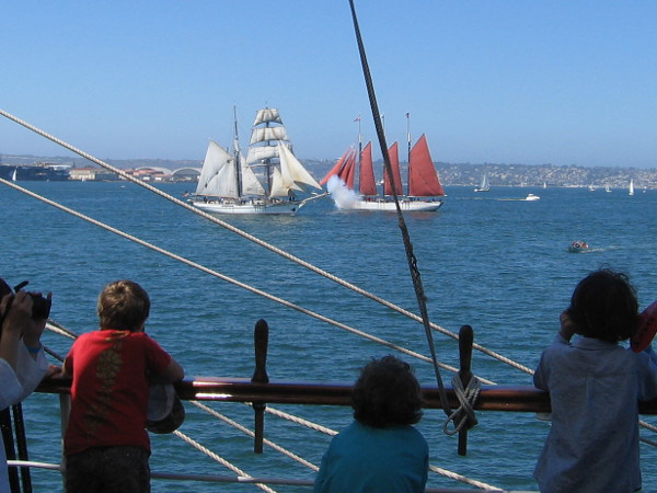 Kids on deck of Star of India watch a cannon battle on San Diego Bay.