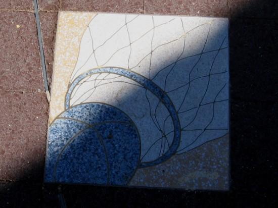A ball and net, half light, half shadow.