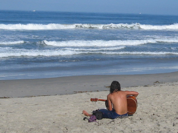 A lone guitarist performs a duet with the mighty ocean.