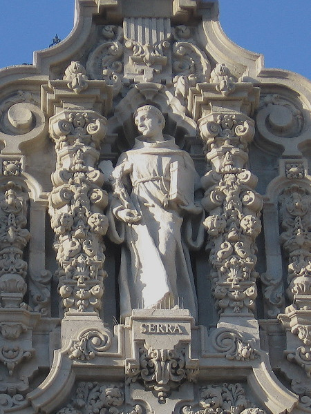 Molded plaster figure of newly canonized Saint Junipero Serra at top of the California Building's facade in Balboa Park.