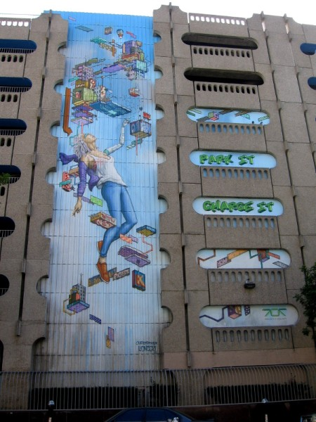 A human connected to technology in this new public art mural. Park it, charge it! The seven-story parking garage is located at 707 Broadway. This photo was taken from 7th Avenue.
